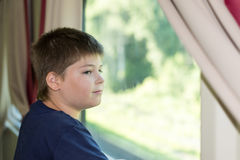 The boy looks out the window on train Royalty Free Stock Image