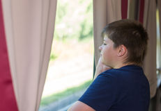 The boy looks out the window on train Stock Images
