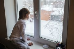Boy looks out the window on a winter day. The boy looks out the window on a winter day. Back view Royalty Free Stock Images