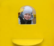 The boy looks out of a yellow window. Royalty Free Stock Photos