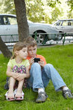 Boy looks at phone screen, sister sits next to him. Boy looks frowning at the phone screen, his younger sister sits next to him on grass and looks over his arm Stock Photos
