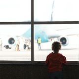 Boy looks at the plane. At the airport silhouette shot from back Stock Photos