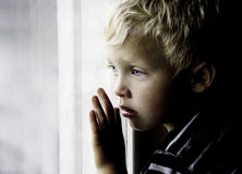 Boy looks sadly through window. The light drops shadows on the face Royalty Free Stock Images