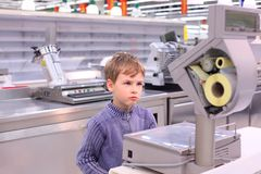 Boy looks at scales in empty shop Royalty Free Stock Images