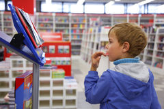 Boy looks at show-windom, bookshop. Bookshop, boy in blue jacket with surprise looks at show-window Royalty Free Stock Photos