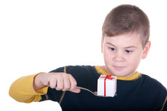 Boy looks at a spoon with a gift. On a white background Royalty Free Stock Images