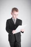 Boy looks at the stack of papers Stock Images