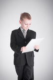 Boy looks at the stack of papers Stock Photo
