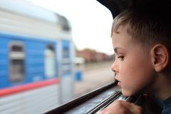 Boy looks in train`s window Stock Images
