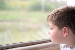 Boy looks in train window Stock Image