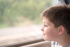 Boy looks in train window Stock Images