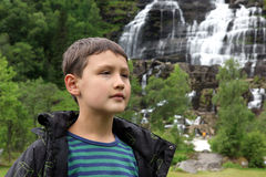 Boy looks at Tvindefossen wild waterfall in Norway Stock Photography