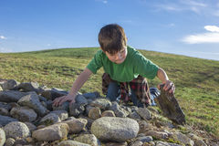 Boy looks under a rock. Stock Photography