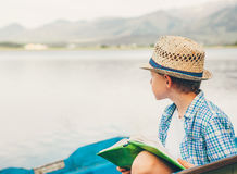 Boy lost in mind sits in the old boat with book Stock Photo
