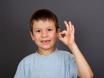 Boy with lost tooth on thread Royalty Free Stock Image