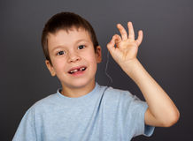Boy with lost tooth on thread Royalty Free Stock Photography