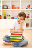 Boy with lots of books thinking Royalty Free Stock Photos