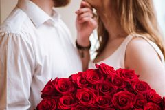 The guy gives the girl a big bouquet of roses 2 royalty free stock images