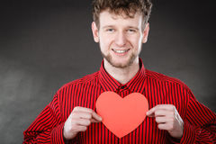 Boy in love with red heart. Love and help from people. Charming lovely man with red paper heart persuade to be good helpful hopeful. Valentines Day or charity Royalty Free Stock Photography