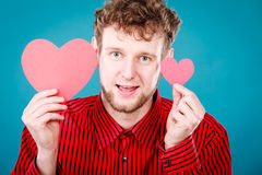 Boy in love with red heart. Love and help from people. Charming lovely man with two red paper hearts persuade to be good helpful hopeful. Valentines Day or Stock Image