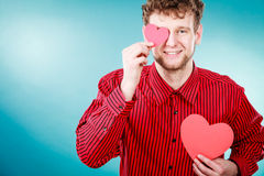 Boy in love with red heart. Love and help from people. Charming lovely man with two red paper hearts persuade to be good helpful hopeful. Valentines Day or Royalty Free Stock Image