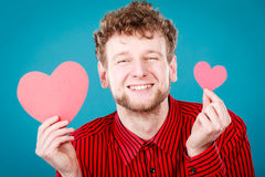 Boy in love with red heart. Love and help from people. Charming lovely man with two red paper hearts persuade to be good helpful hopeful. Valentines Day or Stock Photography
