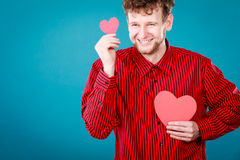 Boy in love with red heart. Love and help from people. Charming lovely man with two red paper hearts persuade to be good helpful hopeful. Valentines Day or Stock Photos