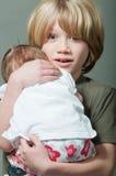 Boy lovingly holding his new born baby sister Royalty Free Stock Photos