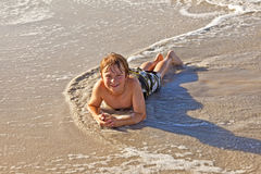 Boy Lying At The Beach And Enjoying The Sun Stock Photo