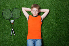 Boy lying with badminton racket on green grass Stock Images