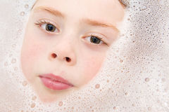 Boy lying in bathtup with bubbles surrounding face. Close up portrait of a young boy lying in the bathtub. Hehas ginger hair and brown eyes with freckles on his stock photo