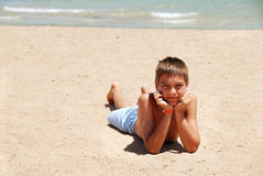 Boy lying on the beach Stock Image