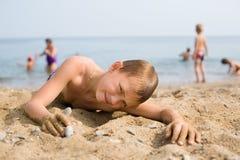 Boy lying on the beach Stock Photos