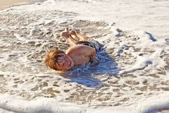 Boy lying at the beach and enjoying the sun Royalty Free Stock Image