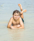 Boy is lying at the beach Stock Images
