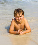 Boy is lying at the beach and enjoys the water and looking self Royalty Free Stock Image