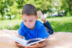 Boy lying on beach mat and reading book. Seriously. Selective focus stock photo