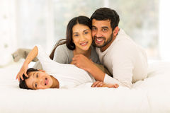 Boy lying bed parents Stock Images