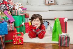 Boy Lying Besides Stacked Christmas Gifts Stock Image