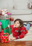 Boy Lying Besides Stacked Presents Royalty Free Stock Photography