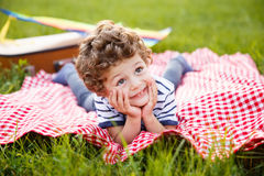 Boy lying on blanket outdoors Stock Images