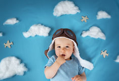 Boy lying on blanket with white clouds Stock Photos