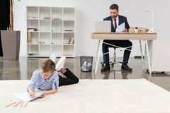 Boy lying on carpet and drawing while his father businessman working stock image