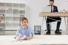 Boy lying on carpet and drawing while his father businessman working stock images