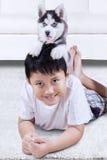 Boy lying on the carpet with husky dog Stock Photos