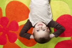 Boy lying on colorful carpet. Portrait of cute boy lying on colorful carpet Stock Photography