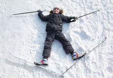 Boy lying in cross-country skis on snow Stock Photos