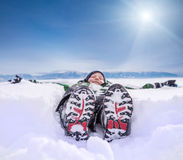 Boy lying in deep snow on the mountain hill Royalty Free Stock Photo
