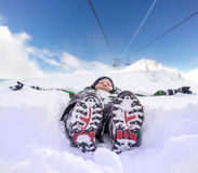 Boy lying in deep snow on the mountain hill Stock Photo