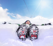 Boy lying in deep snow on the mountain hill Royalty Free Stock Photos